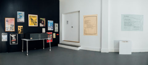 Installation photo of a corner in the gallery with one black wall and one white, with historical artist-activist ephemera hung salon style on the wall.