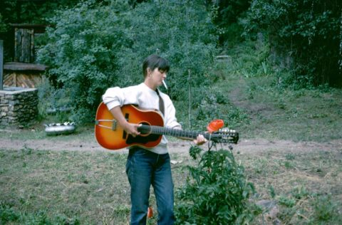 A woman in jeans stands alone near the woods, playing a guitar and smoking a cigarette.